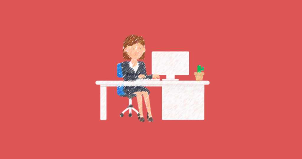 Corporate woman in suit sitting at computer, cactus also on desk